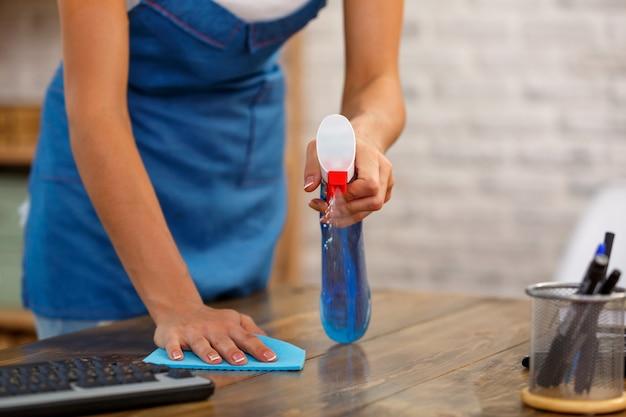 Studioaufnahme der haushälterin hautnah. schöne frau reinigungstisch mit spray. konzentriere dich auf die hände