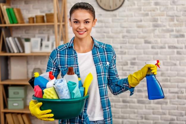 Studioaufnahme der haushälterin. schöne frau reinigungsraum. frau trägt handschuhe, lächelt und hält eine schüssel voller flaschen mit desinfektionsmittel