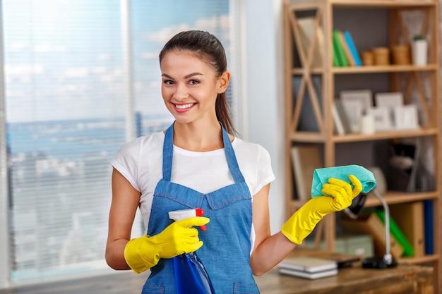 Studioaufnahme der haushälterin. schönheitsreinigungsbüro. frau trägt handschuhe, lächelt und hält eine flasche mit desinfektionsmittel