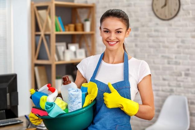 Studioaufnahme der haushälterin. schönheitsreinigungsbüro. frau trägt handschuhe, lächelt, zeigt daumen nach oben und hält eine schüssel voller flaschen mit desinfektionsmittel
