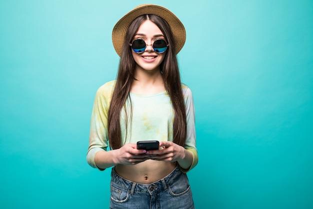 Studioaufnahme der hübschen jungen lachenden europäischen frau, die perfektes zahnlächeln zeigt, nachricht an freund auf handy tippend, gadget mit einer hand lokalisiert auf grün hält