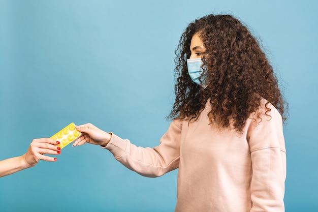 Studioaufnahme der infizierten frau mit pillen in den händen, dame, die schützende gesichtsmaske trägt