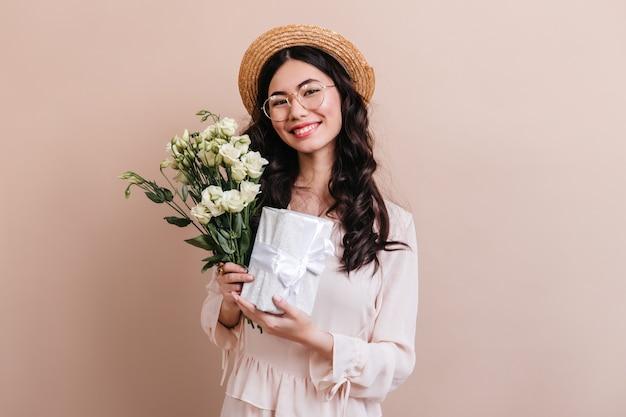 Studioaufnahme der japanischen frau mit weißen blumen. charmantes asiatisches modell, das eustoma blumenstrauß und geschenk hält.