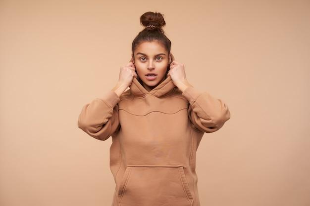 Studioaufnahme der jungen braunhaarigen frau mit natürlichem make-up, das hände auf ihrer kapuze hält, während sie aufmerksam nach vorne schaut und über beige wand steht