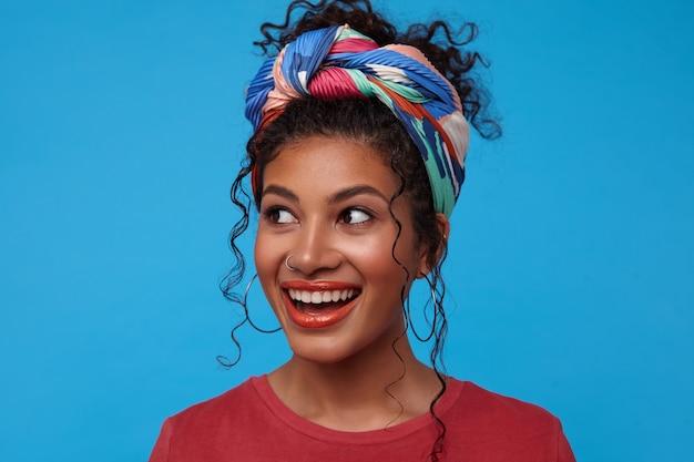 Studioaufnahme der jungen reizenden brünetten lockigen dame mit gesammeltem haar gekleidet in farbigen trendigen kleidern, die fröhlich mit breitem lächeln beiseite schauen, lokalisiert über blauer wand