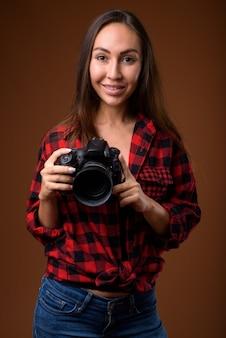 Studioaufnahme der jungen schönen frau mit kamera gegen braunen hintergrund