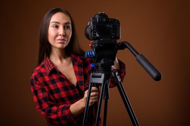 Studioaufnahme der jungen schönen frau vlogging gegen braunen hintergrund