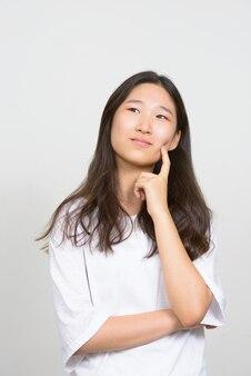 Studioaufnahme der jungen schönen koreanischen frau gegen weißen hintergrund