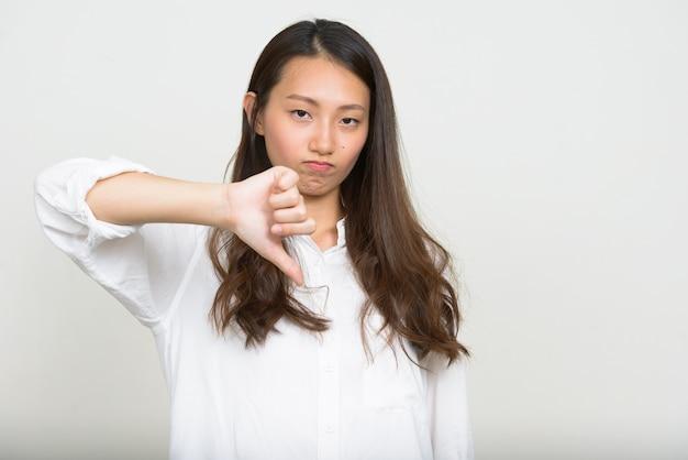 Studioaufnahme der jungen schönen koreanischen geschäftsfrau gegen weißen hintergrund