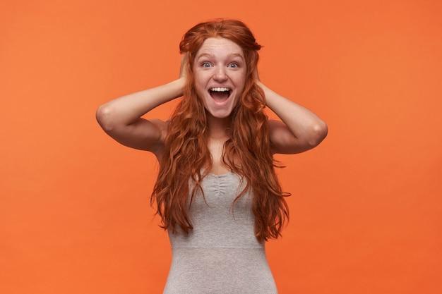 Studioaufnahme der reizenden überglücklichen jungen frau mit gewelltem foxy lond haar, das über orange hintergrund aufwirft, fröhlich zur kamera schaut und ihren kopf mit hält, glücklich zum wahnsinn ist