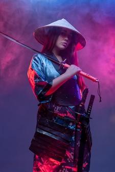 Studioaufnahme der samurai-frau mit katana, die vor buntem hintergrund mit rauch aufwirft.