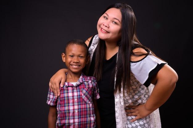 Studioaufnahme der schönen übergewichtigen asiatischen frau und des jungen multiethnischen asiatischen jungen zusammen vor schwarzem hintergrund