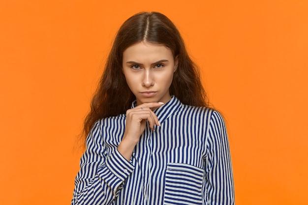 Studioaufnahme der selbstbewussten gut aussehenden attraktiven jungen frau, die stilvolles gestreiftes hemd trägt