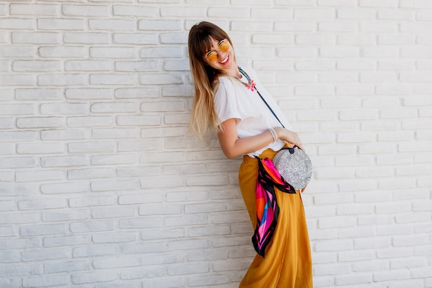 Studioaufnahme der sorglosen frau im hellen sommeroutfit, das über weiße backsteinmauer aufwirft Kostenlose Fotos