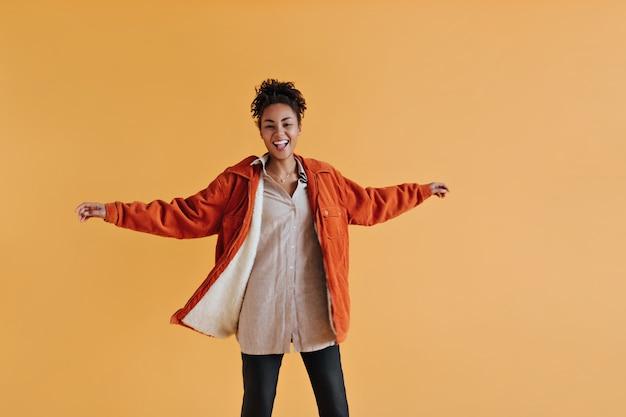 Studioaufnahme der stilvollen frau, die orange windjacke trägt