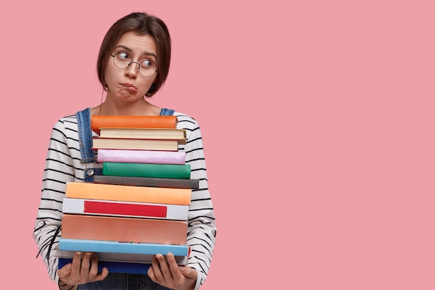Studioaufnahme der unzufriedenen kaukasischen frau beißt sich auf die lippen, trägt eine brille und einen gestreiften pullover, will nicht studieren