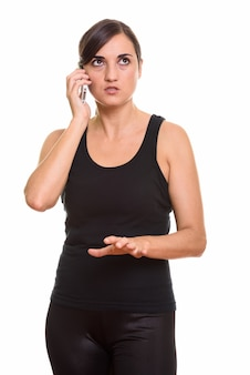 Studioaufnahme der wütenden frau, die auf handy spricht, während sie denkt