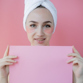 Studioaufnahme der zufriedenen kaukasischen sommersprossigen frau, die weißes handtuch auf kopf trägt, mit kollagenflecken unter den augen, die nackt gegen rosa hintergrund stehen