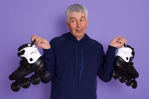 Studioaufnahme des älteren mannes, der sportlichen kapuzenpulli mit rollen in den händen trägt