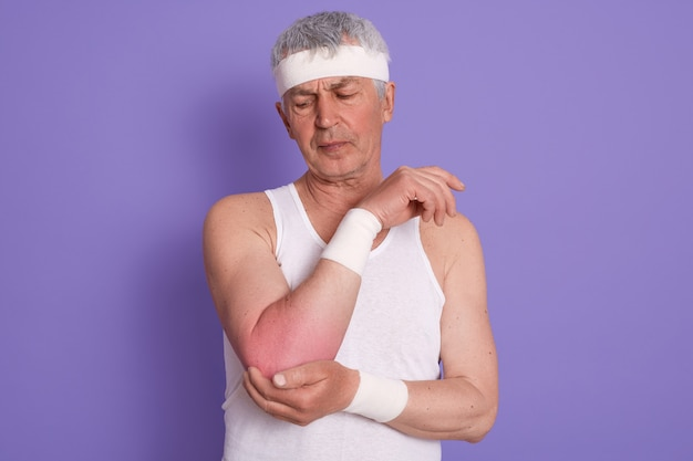 Studioaufnahme des älteren mannes, der weißes ärmelloses t-shirt und stirnband trägt