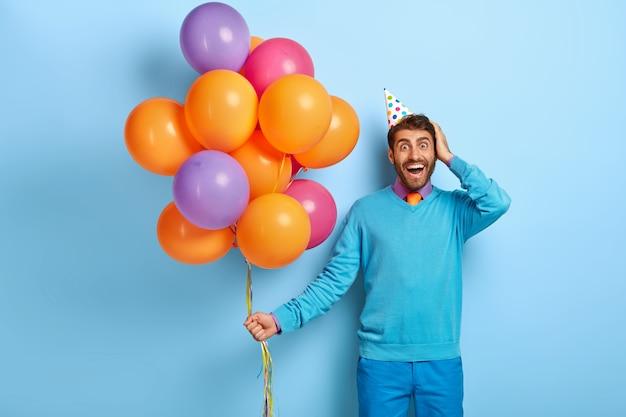 Studioaufnahme des aufgeregten kerls mit geburtstagshut und luftballons, die im blauen pullover aufwerfen