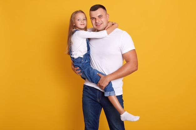 Studioaufnahme des charmanten kindermädchens mit ihrem vater, gutaussehender mann, der kind in händen hält und freizeitkleidung trägt
