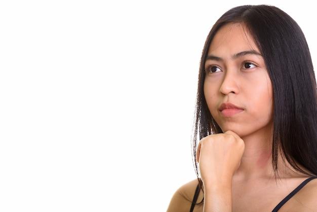 Studioaufnahme des denkens der jungen asiatischen teenagerin