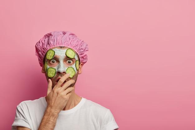 Studioaufnahme des emotionalen europäischen mannes bedeckt mund mit handfläche, schockiert, um informationen von kosmetikerin zu hören, trägt gurken und tonmaske auf gesicht auf