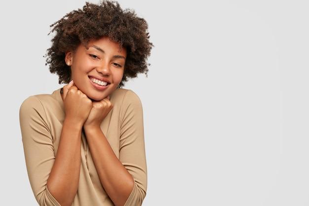 Studioaufnahme des erfreuten emotionalen jungen weiblichen afro-modells hält kinn