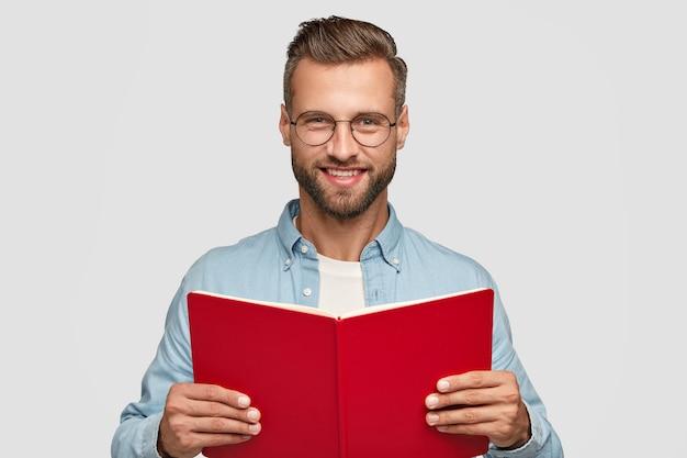 Studioaufnahme des fröhlichen mannlesers mit zufriedenem ausdruck, hält rotes buch