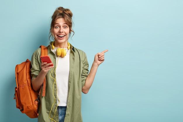 Studioaufnahme des glücklichen jungen mädchens hält handy, prüft e-mail, erhält neue benachrichtigung, verwendet moderne kopfhörer, zeigt auf kopierplatz für markennamen oder etikett, trägt loses khakihemd, trägt tasche
