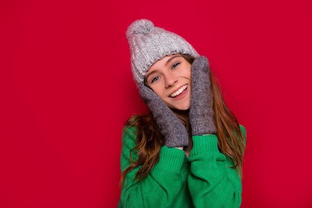 Studioaufnahme des glücklichen lächelnden mädchens mit entzückendem lächeln und den blauen augen, die ihr gesicht gekleidete wintermütze und fäustlinge auf lokalisiertem rotem hintergrund berühren