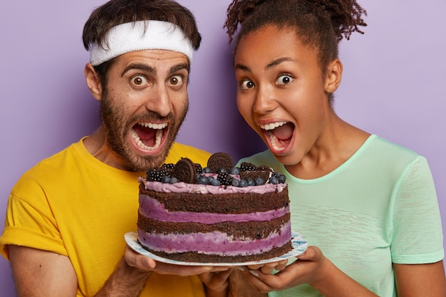 Studioaufnahme des glücklichen überglücklichen multiethnischen paares halten köstlichen kuchen mit blaubeeren