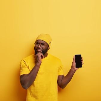 Studioaufnahme des gutaussehenden mannes mit brille, die mit seinem telefon aufwirft