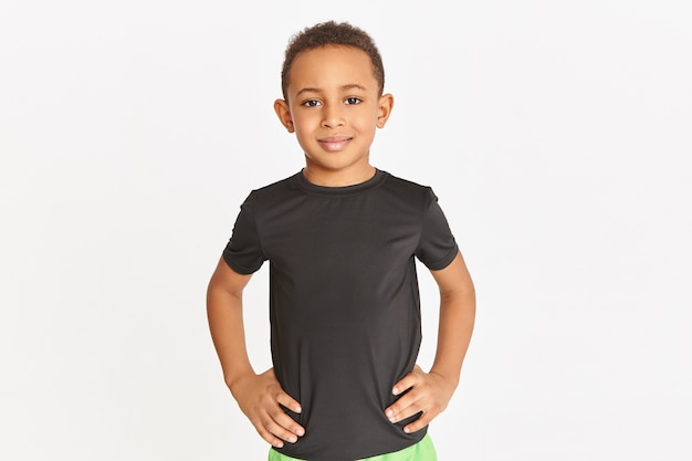 Studioaufnahme des hübschen athletischen dunkelhäutigen kleinen jungen, der isoliert im schwarzen t-shirt posiert und hände auf seiner taille hält und drinnen trainiert.
