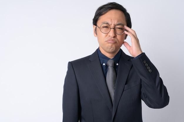 Studioaufnahme des japanischen geschäftsmanns, der anzug gegen weißen hintergrund trägt
