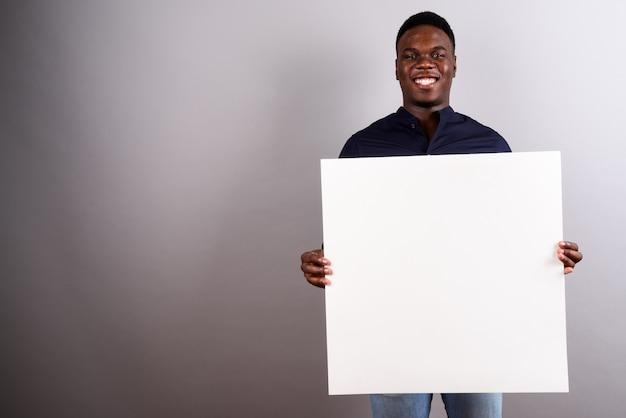 Studioaufnahme des jungen afrikanischen geschäftsmannes, der weiße tafel gegen weißen hintergrund hält