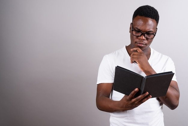Studioaufnahme des jungen afrikanischen mannes, der brillen trägt, während buch vor weißem hintergrund liest