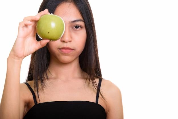 Studioaufnahme des jungen asiatischen teenager-mädchens, das auge mit grünem apfel bedeckt