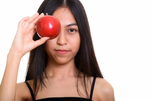 Studioaufnahme des jungen asiatischen teenager-mädchens, das auge mit rotem apfel bedeckt