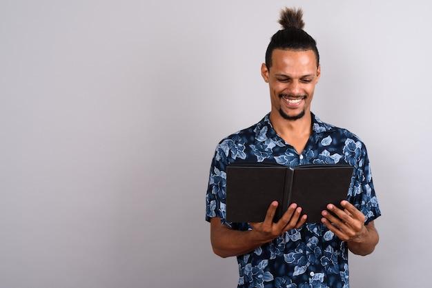 Studioaufnahme des jungen bärtigen gutaussehenden afrikanischen mannes, der buch gegen grauen hintergrund liest