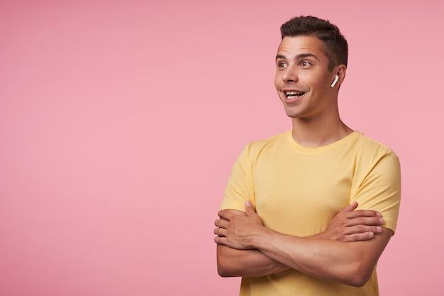 Studioaufnahme des jungen brünetten mannes mit kopfhörern, die emotional nach vorne mit breitem lächeln schauen und hände gefaltet auf brust halten, lokalisiert über rosa hintergrund