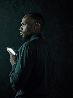 Studioaufnahme des jungen ernsthaften schwarzafrikaners, der denkt, während er auf handy gegen schwarzen studiohintergrund spricht