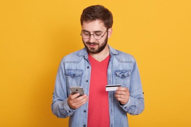 Studioaufnahme des jungen europäischen bärtigen mannes, der kreditkarte und smartphone hält und mit ruhigem gesichtsausdruck über gelb steht