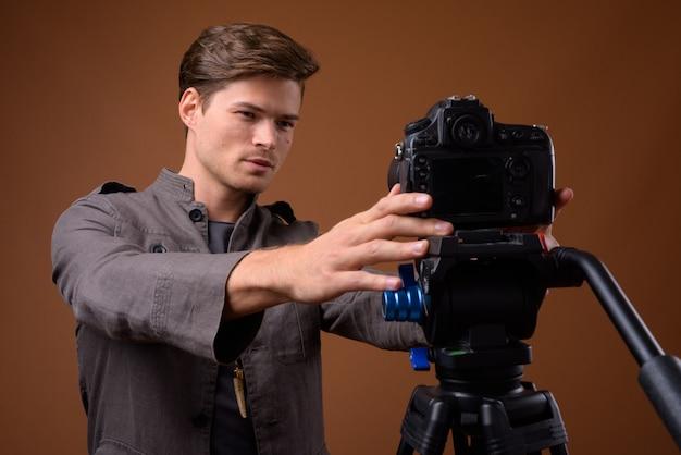 Studioaufnahme des jungen gutaussehenden mannes, der mit kamera vloggt
