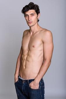 Studioaufnahme des jungen gutaussehenden mannes ohne hemd mit den händen auf der tasche