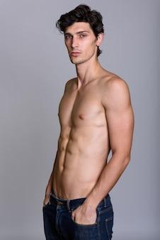 Studioaufnahme des jungen gutaussehenden mannes ohne hemd