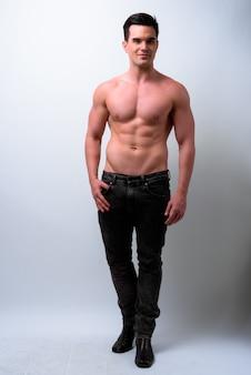 Studioaufnahme des jungen gutaussehenden muskulösen mannes hemdlos gegen weißen hintergrund