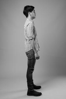 Studioaufnahme des jungen gutaussehenden philippinischen mannes gegen grau in schwarzweiss