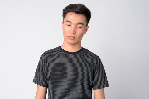 Studioaufnahme des jungen hübschen asiatischen mannes gegen weißen hintergrund